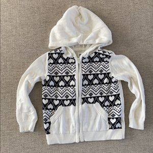 White hooded sweater with black heart design.